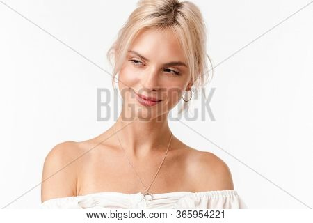 Image of happy blonde woman in earrings smiling and looking aside isolated over white background
