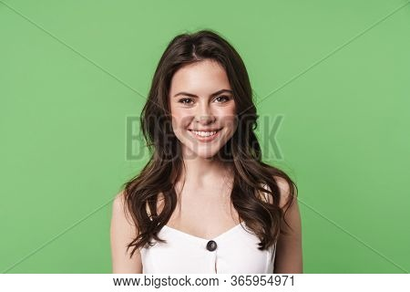 Image of happy caucasian woman smiling and looking at camera isolated over green background