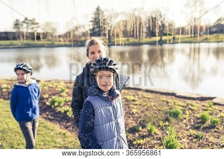 Mom With Her Two Boys Taking A Stroll In A Park