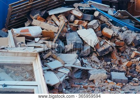 A Pile Of Construction Waste Near Private House. Building Rubble, Bricks, Stones. Junk, Garbage Pile