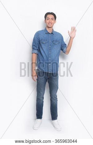 full length young man wearing jeans blue shirt with blue jeans with sneakers with making stop gesture