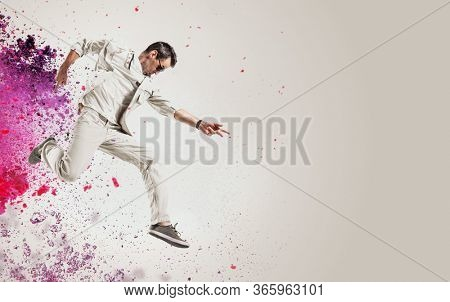 Young jumping man over colorfull background
