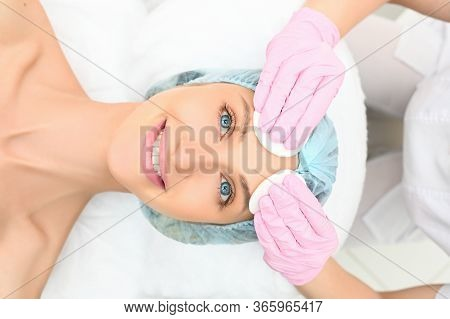Beautiful Happy Woman Receiving Spa Treatment. Cosmetologist In Beauty Salon Cleaning Womans Face. F