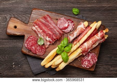 Meat, salami and prosciutto antipasto. Appetizer selection on wooden board. Top view flat lay