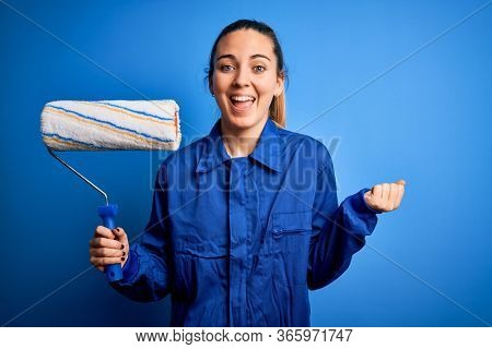 Young beautiful blonde painter woman with blue eyes painting wearing uniform using roller screaming proud and celebrating victory and success very excited, cheering emotion