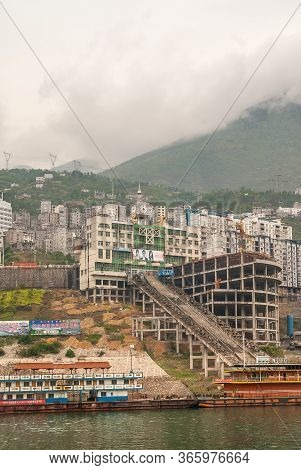 Xinling, China - May 6, 2010: Xiling Gorge On Yangtze River. Clock Tower Behind Construction Site On
