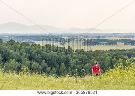 Girl In Red Descends From A Hill Expanses Of Meadows And Forests Mountains Are Visible, Selective Fo
