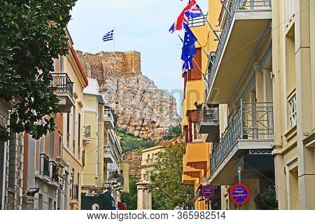 Looking Down An Athens, Greece City Street Lined With Homes And A View Of The Outer Wall Of Acropoli
