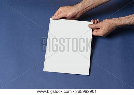 Male Hands Holding A Closed Book-catalog With Blank Cover On Blue Background, Mock-up Series Templat