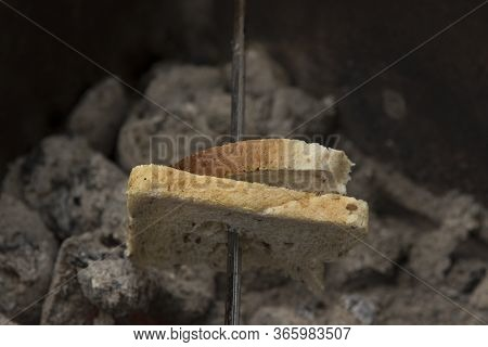 On The Brazier, On The Fire, Almost Extinguished With Coals, Slices Of Bread Is Fried On A Skewer. A