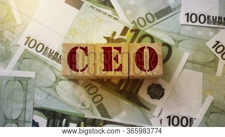 Ceo Written On A Wooden Cube On 100 Euro Bills. Letters Stands For Chief Executive Officer. Business