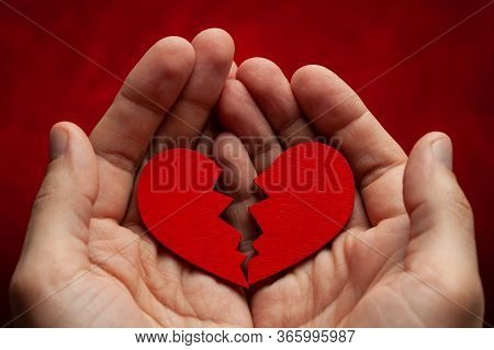 Man Holds A Broken Heart In His Hands. Crack In The Red Heart, Breaking The Relationship