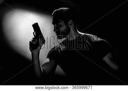 Bw Portrait Of Serious Young Man Holding Gun On Dark Background