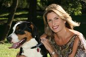Gorgeous woman with her swiss mountain dog having fun outdoors in a pakr poster