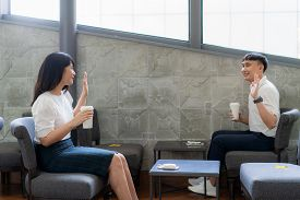 Asian Young Man And Woman Sitting One Person Per One Table And Greet And Say Hello For Distance Of 6