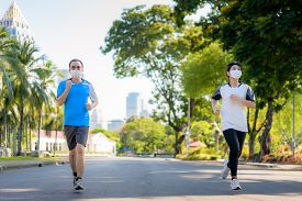 Asian Young Couple Woman And Man Are Jogging And Exciseing Outdoor In City Park And Wearing Protecti