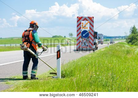 Road landscapers cutting grass around mileposts along the road using string lawn trimmers poster