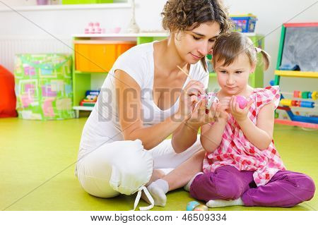 Young Mother And Daughter Painting Easter Eggs