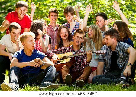 Amigos de escola feliz cantando por guitarra