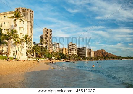 Tourist Sunbathing And Surfing On The Waikiki Beach In Hawaii With Diamond Head In Background.