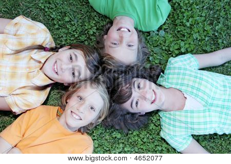 group of happy kids youth tweens or children laying down looking up with smiling faces poster