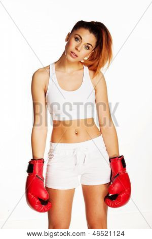 Pretty woman with fallen arms wearing boxing gloves and white shorts and a top showing tiredness isolated on a white background