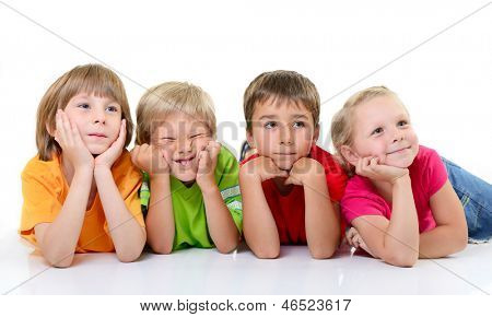 cute funny children in colored t-shirts lying and with interest looking right, over white background