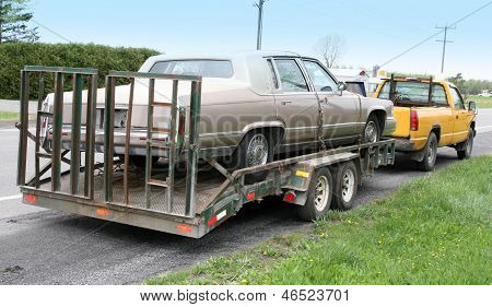 Old cadillac towed by truck