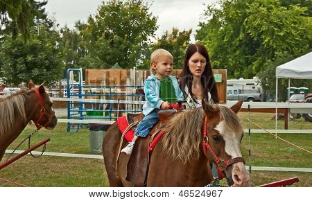 poster of This 1 year old toddler girl is riding a first pony ride with her mom walking beside her. Rural lifestyle family image.