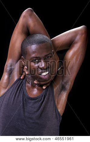 Portrait of young athletic black man with arms tangled behind head as he grabs his neck displaying anxiety and unrest on black background poster
