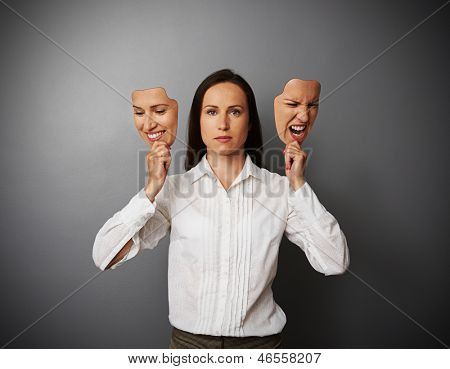 serious woman holding two masks with different mood