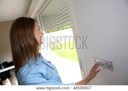 Woman lifting electric shutters in house