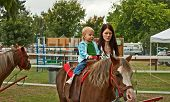 This 1 year old toddler girl is riding a first pony ride with her mom walking beside her. Rural lifestyle family image. poster