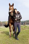 equestrian with her horse on meadow poster