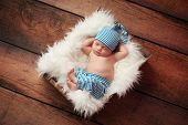 Newborn baby sleeping in a wooden crate on faux fur wearing blue and white striped pajamas with matching sleeping cap. poster