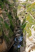 Deep gorge El Tajo in Ronda Spain with stream poster