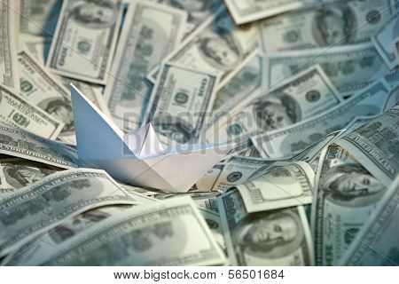 Paper ship at sea of money