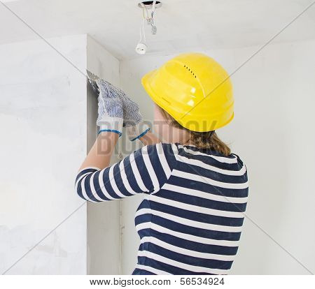 Female Plasterer Repairs Wall With Spackling Paste