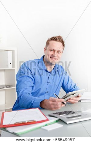 Smiling Businessman Working At His Desk
