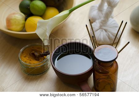 A countertop arrangement of ayurvedic turmeric spice oil and massaging tools and an exotic flower used in Ayurveda massage. poster