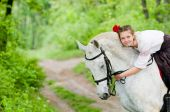 Cute girl riding horse in the forest poster