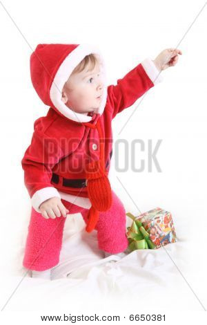 Little Girl In Santa's Clothes With Present