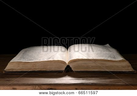 Old book on table on black background