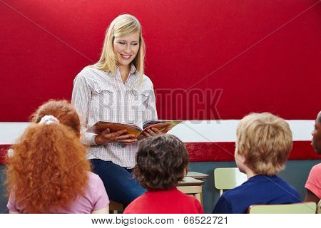 Elementary school teacher reading from book in class to students