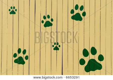 Paw prints on yellow fence