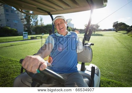 Golfer driving his golf buggy and smiling at camera on a sunny day at the golf course