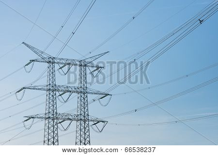 High voltage lines insulators and a power pylon against a blue sky on a sunny day in the summer season. poster