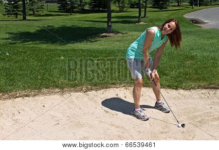 Woman Prepares To Swing At The Golf Ball Caught In The Sand Trap