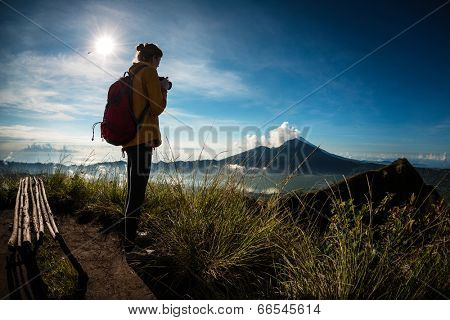 Hiker with photo camera standing on top of the mountain and enjoying view