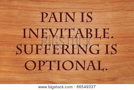 Pain is inevitable. Suffering is optional. - quote on wooden red oak background